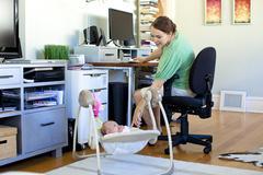 Valkoihoinen äiti työskentelee kotitoimistoon vauva hänen vieressään Kuvituskuvat