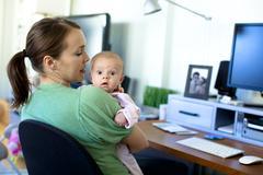 Valkoihoinen äiti työskentelee kotona toimistossa ja tilalla vauva Kuvituskuvat