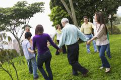 Hispanic family holding hands in a circle outdoors Stock Photos