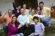 Hispanic family sitting on steps together waving Stock Photos
