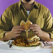 Overweight man eating hamburgers and french fries Stock Photos