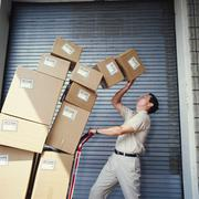 boxes tipping on delivery man - stock photo