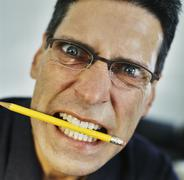 Angry businessman with pencil in mouth Stock Photos