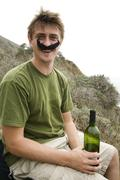Caucasian man in costume mustache holding wine bottle Stock Photos