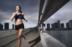 Hispanic woman running near urban waterfront Stock Photos