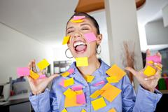 Hispanic businesswoman covered in sticky notes Stock Photos