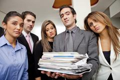 frustrated hispanic business people with pile of paperwork - stock photo
