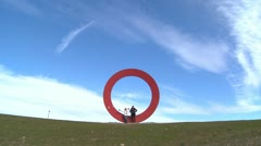 Two people sit on a sculpture of the letter o against an open sky. - stock footage
