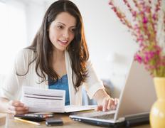 Brazilian woman paying bills online Stock Photos