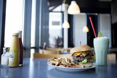 Cheeseburger, french fries and milkshake in diner Stock Photos