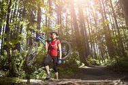 Hispanic woman carrying mountain bike in forest Stock Photos