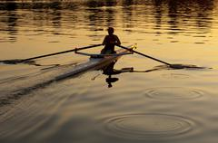 Person rowing sculling boat on river Stock Photos