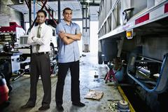 Manager and mechanic standing in auto repair shop Stock Photos