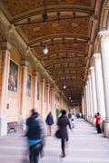 People walking underneath ornate portico Stock Photos