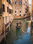 Gondolier rowing gondola in canal Stock Photos