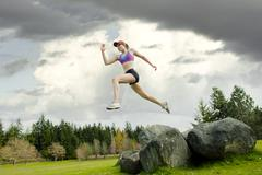 Mixed race teenager jumping from rock - stock photo