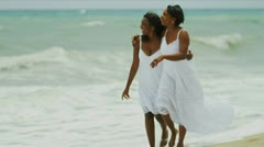 Ethnic mother daughter spending time together walking on beach   - stock footage