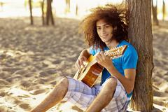 Mixed race teenager sitting in sand strumming guitar Stock Photos