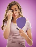 Caucasian teenager putting on mascara Stock Photos