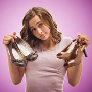 Uncertain Caucasian teenager holding shoes Stock Photos