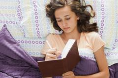 Caucasian teenager laying in bed writing in journal Stock Photos