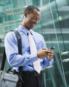 Black businessman text messaging on cell phone - stock photo