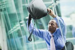 Black businessman turning briefcase upside-down looking for something Stock Photos