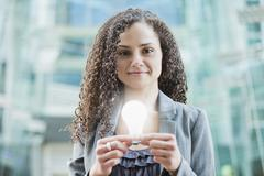 Caucasian businesswoman holding glowing light bulb Stock Photos