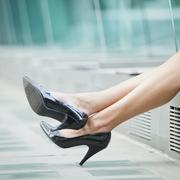 Caucasian businesswoman's legs wearing high heeled shoes Stock Photos