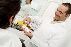Hispanic Barber squirting saving cream into hand Stock Photos