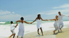 African American family together playing and laughing by ocean   Stock Footage
