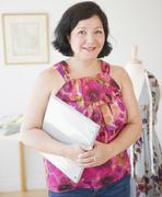 Hispanic clothes designer holding notebook Stock Photos