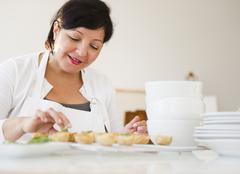 Smiling Hispanic woman baking Stock Photos