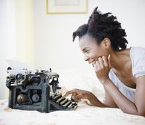 Black woman using old-fashioned typewriter Stock Photos