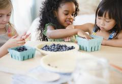 Girls putting blueberries into bowl together - stock photo
