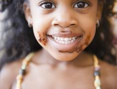 Mixed race girl with chocolate on her face Stock Photos