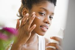 Black woman putting on face lotion Stock Photos