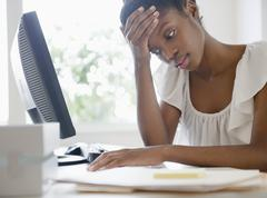 Frustrated Black businesswoman working at desk Stock Photos