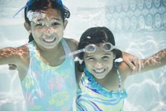Hispanic girls swimming under water Stock Photos