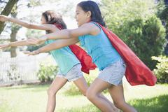 Hispanic girls in capes playing superheroes - stock photo