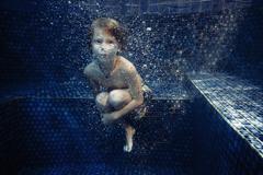Boy swimming underwater in swimming pool Stock Photos
