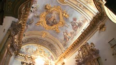 The interior of a small ornate Catholic church with beautiful paintings on - stock footage