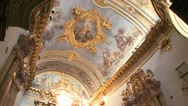 The interior of a small ornate Catholic church with beautiful paintings on Stock Footage