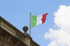 Italian flag fluttering on rooftop Stock Photos