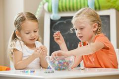 Caucasian sisters playing with beads Stock Photos