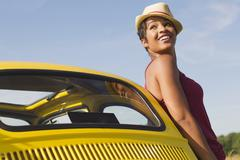 Smiling mixed race woman leaning on car Stock Photos