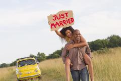 Man piggybacking wife who is holding just married sign Stock Photos