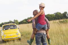 Man piggybacking wife in field near car - stock photo
