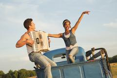 Man playing accordion for girlfriend in back of truck - stock photo