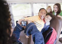 Tyttö ottaa valokuvia koulubussi Kuvituskuvat